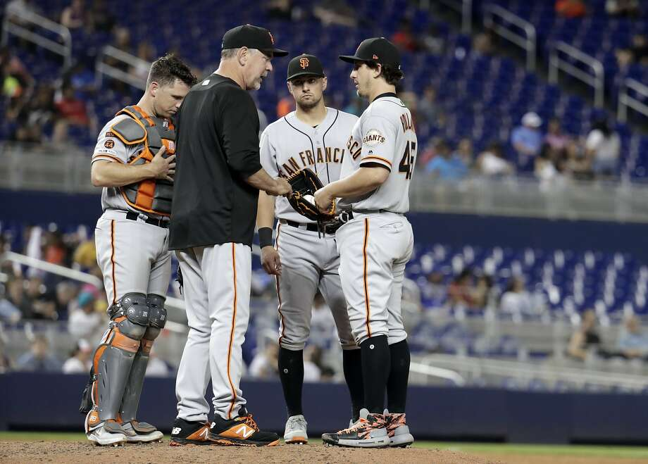 San Francisco Giants manager Bruce Bochy, second from left, talks with relief pitcher Derek Holland, right, during the sixth inning of a baseball game against the Miami Marlins, Tuesday, May 28, 2019, in Miami. (AP Photo/Lynne Sladky) Photo: Lynne Sladky / Associated Press