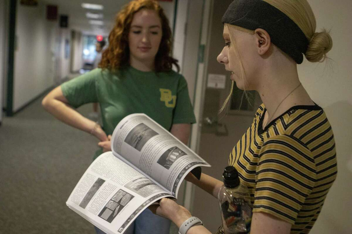 iSchool High junior Courtney Brumley flips through a textbook used by the school Wednesday, May 22, 2019 at Lone Star College - Montgomery in The Woodlands.