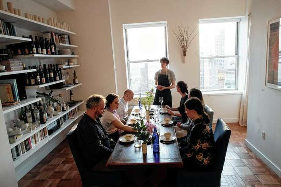 Jonah Reider (standing) talks to his guests about the dinner he is serving them in his New York apartment. His new mission: to inspire people to do relaxed home cooking for friends and family rather than overspending at fancy restaurants. Photo: Mary Altaffer | Associated Press
