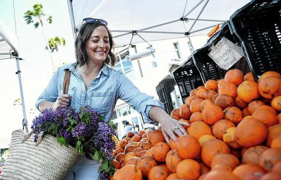 """Gaby Dalkin shops for oranges at the Santa Monica Downtown Farmers Market in Santa Monica, California. Dalkin, the chef behind the popular Website and social media accounts, """"What's Gaby Cooking,"""" is forging her own path. Every Monday she posts a live demo to Instagram as she cooks dinner. It has become appointment viewing for some fans Photo: Chris Pizzello 