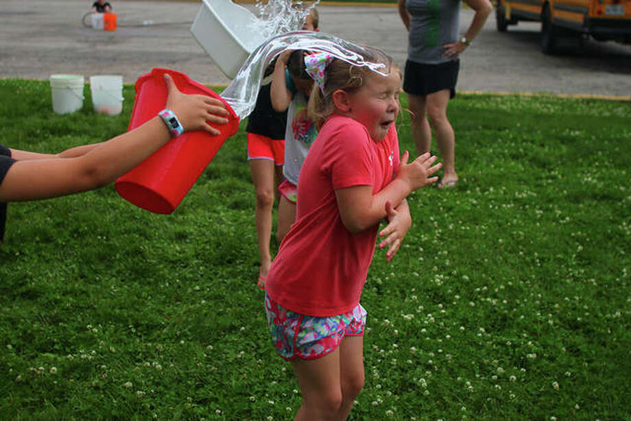A bucket of water is dumped on Our Saviour School first-grader Reese Wisdom during an activity day Tuesday. Photo: Rosalind Essig | Journal-Courier