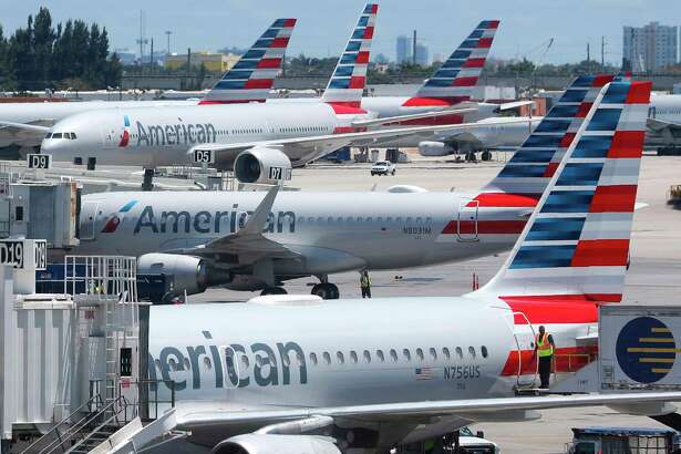 In this Wednesday, April 24, 2019, photo, American Airlines aircraft are shown parked at their gates at Miami International Airport in Miami. American Airlines is accusing its mechanics and their unions of conducting an illegal work slowdown to gain leverage in contract talks, and the airline is asking a federal judge to stop the activity.