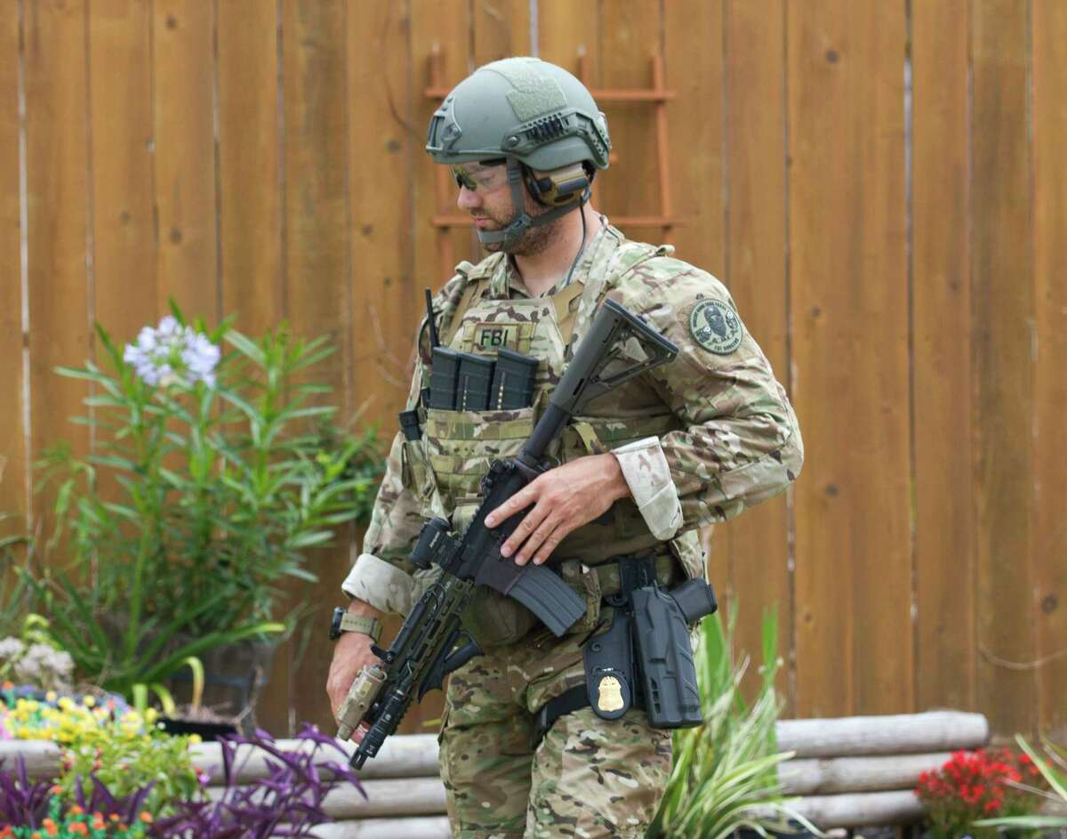 A member of the Houston's FBI violent gang task force helps search homes along Highway 2247 after a suspect's vehicle from an officer involved shooting was found nearby, Wednesday, May 29, 2019, in Cleveland.