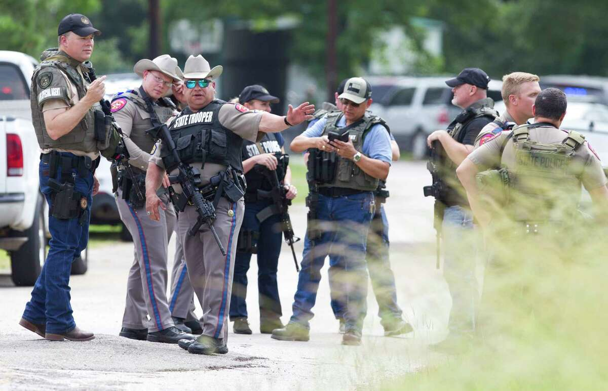 Law enforcement search homes along Highway 2247 after a suspect's vehicle from an officer involved shooting was found nearby, Wednesday, May 29, 2019, in Cleveland.