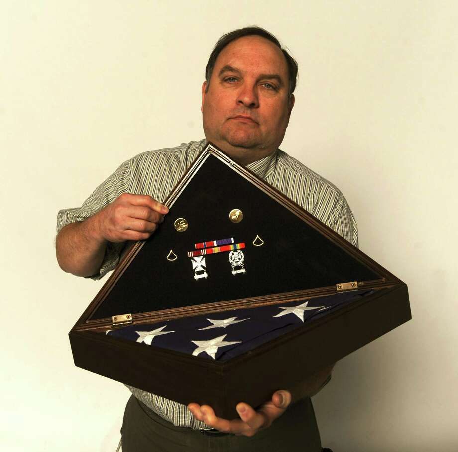 Patrick Miller displays decorations and the flag that draped the casket of his son, Army Pfc. Anthony Scott Miller, who died at age 19 on April 7, 2003, the first San Antonio native to die in the Iraq War. Photo: Billy Calzada /Staff File Photo / gcalzada@express-news.net