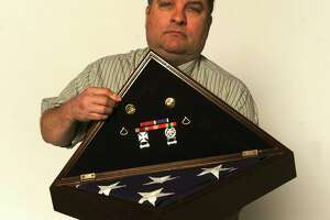 Patrick Miller displays decorations and the flag that draped the casket of his son, Army Pfc. Anthony Scott Miller, who died at age 19 on April 7, 2003, the first San Antonio native to die in the Iraq War.
