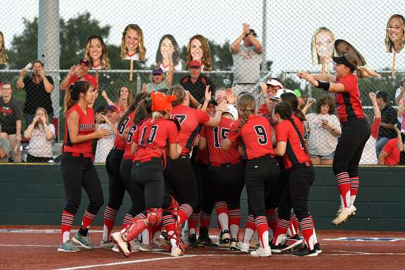 Huffman sophomore Hagen Pike, right, and her teammates congratulate junior outfielder Kenzie Gates (15) as she touches home plate after homering against Robinson in the top of the 4th inning of Game One of their Region III-4A Final Playoff Series at Madisonville High School on May 23, 2019.