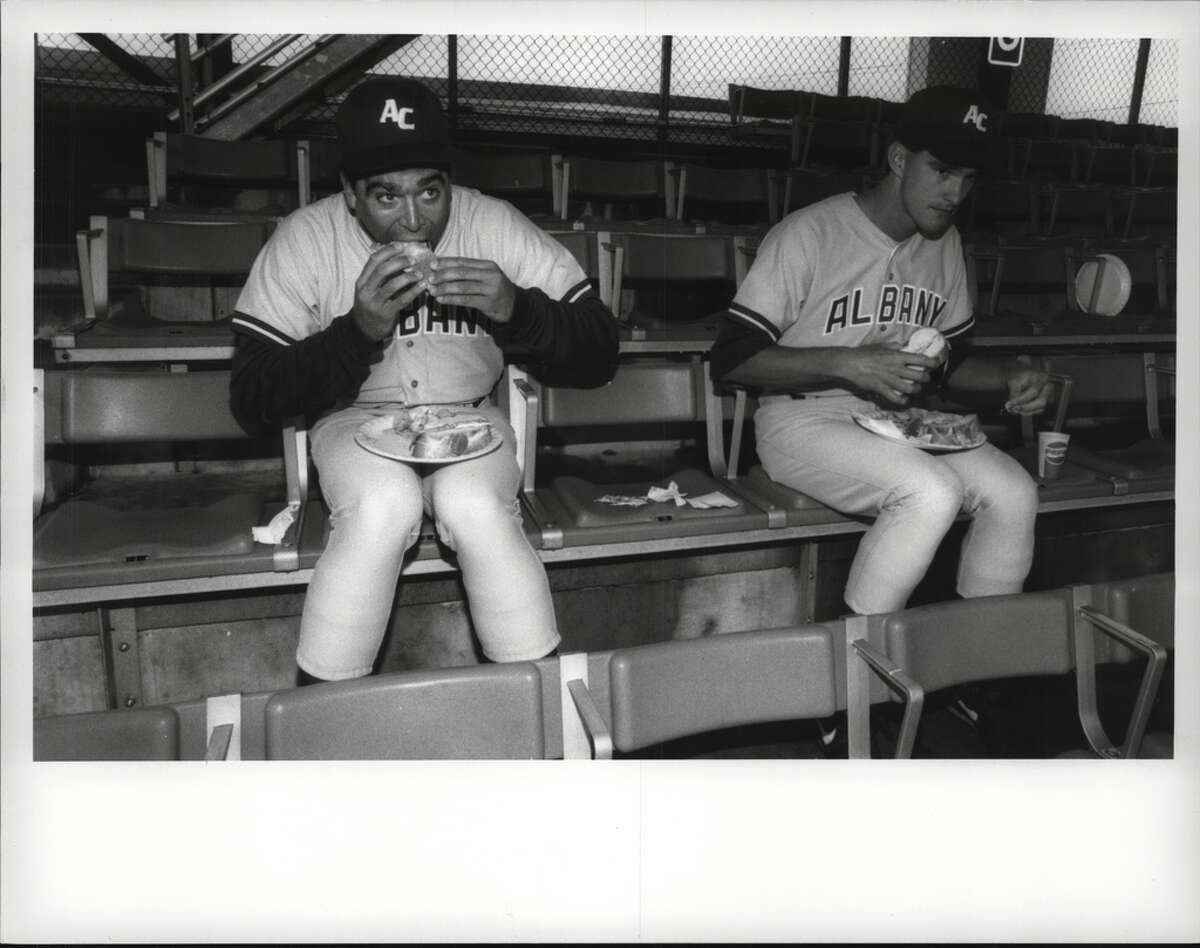 Kevin Mmahat and Rodney Imes of the Albany-Colonie Yankees eat free food at a press conference.