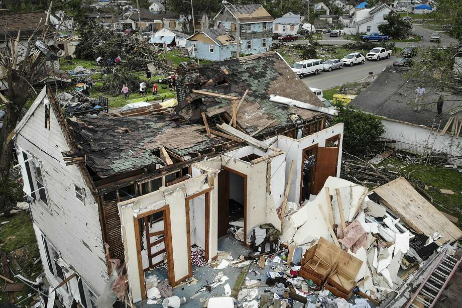 Repair and cleaning efforts begin on a neighborhood damaged by a tornado storm system that passed through the area, destroying homes and cutting off access to utilities in Dayton, Ohio. Photo: John Minchillo / Associated Press