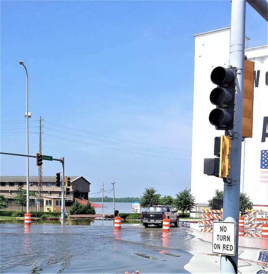 Worker to help with flood drives through high water