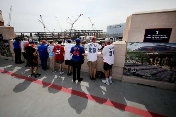 ARLINGTON, TEXAS - MARCH 28: Fans observe the construction site of the new Globe Life Field before the Texas Rangers take on the Chicago Cubs during Opening Day at Globe Life Park in Arlington on March 28, 2019 in Arlington, Texas. (Photo by Tom Pennington/Getty Images)