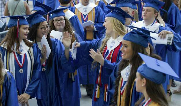 Toni Do, second from left, dances across from Rebecca Miess before a graduation ceremony for Oak Ridge High School at Cynthia Woods Mitchell Pavilion, Tuesday, May 28, 2019, in The Woodlands. Photo: Jason Fochtman, Houston Chronicle / Staff Photographer / © 2019 Houston Chronicle