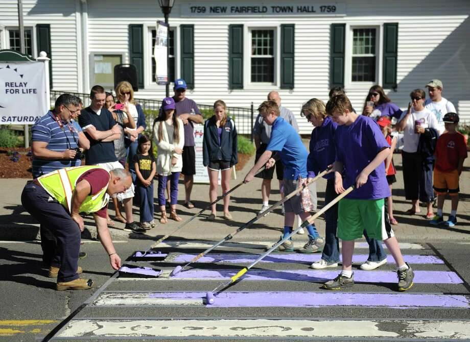 File photo from Saturday, May 31, 2014. New Fairfield residents paint the sidewalk purple to promote next weekend's Relay for Life, outside the town hall in New Fairfield, Conn. The Relay for Life, a fundraiser for the American Cancer Society, will be held at New Fairfield High School on Saturday, June 7 at 3 p.m. Photo: Tyler Sizemore / Tyler Sizemore / The News-Times