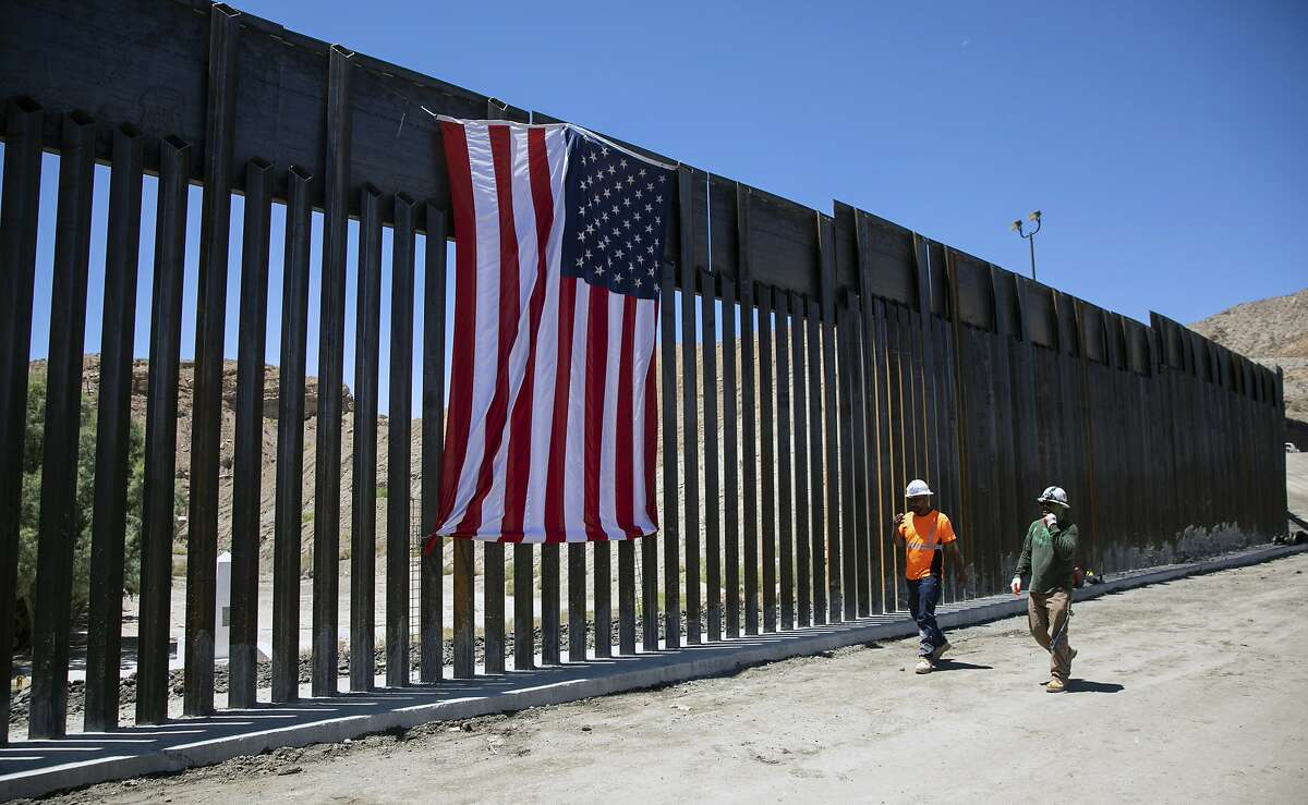 Construction workers walk past a new barrier in Sunland Park, N.M., on the border with Mexico, on Tuesday, May 28, 2019. We Build the Wall, a private group, is constructing less than a mile of border fencing on private land in southern New Mexico. (Ivan Pierre Aguirre/The New York Times)