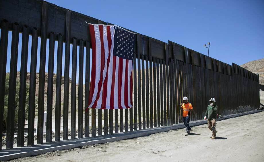 Construction workers walk past a new barrier in Sunland Park, N.M., on the border with Mexico, on Tuesday, May 28, 2019. We Build the Wall, a private group, is constructing less than a mile of border fencing on private land in southern New Mexico. (Ivan Pierre Aguirre/The New York Times) Photo: Ivan Pierre Aguirre, NYT