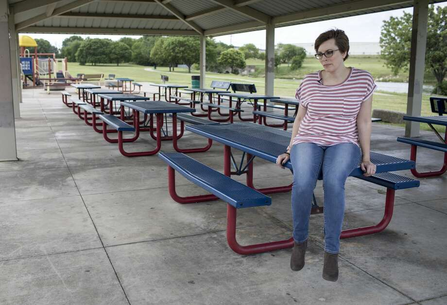 Anne Marie Miller sits on a picnic table at Greenbriar Park in Fort Worth, where she says Mark Aderholt would take her to make out when she was a teenager. Photo: Jon Shapley/Staff Photographer