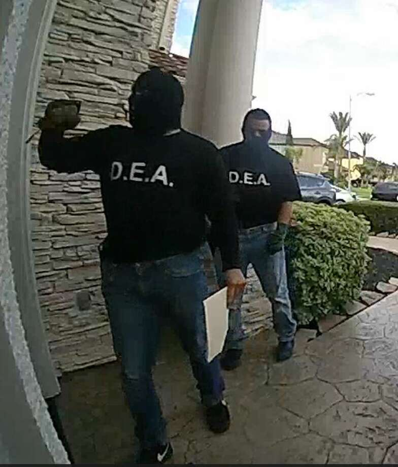 "The two men's disguises consisted of blue jeans and black shirts with ""DEA"" lettering on the front and ""Police"" lettering on the back. Police said both men appeared to be armed with handguns and were wearing balaclavas, also known as ski masks, to cover their faces. Photo: Pearland Police Department"