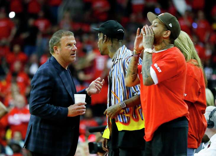 Rockets owner Tilman Fertitta talks to rapper Travis Scott during the third quarter of Game 3 of a NBA Western Conference semifinal playoff game at Toyota Center, in Houston , Saturday, May 4, 2019.