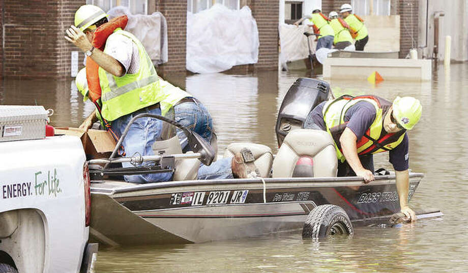 Electrical workers from Ameren have a little trouble getting their boat back onto its trailer Wednesday in the middle of a flooded West Broadway in downtown Alton. The workers had been preparing the mill for more floodwaters after the crest forecast for Tuesday afternoon was again increased, by almost a foot. to 39-feet-3 in Alton. That would put it about 3 feet below the record set in 1993. Ardent Mills workers, background, were raising the level of plastic and wood blocking water from the plant's office building. For additional Alton flooding photos, visit thetelegraph.com.