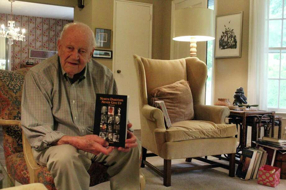 "Westport resident Larry Aasen with his fourth book ""North Dakotans Never Give Up."" Photo: Lynandro Simmons /Hearst Connecticut Media"