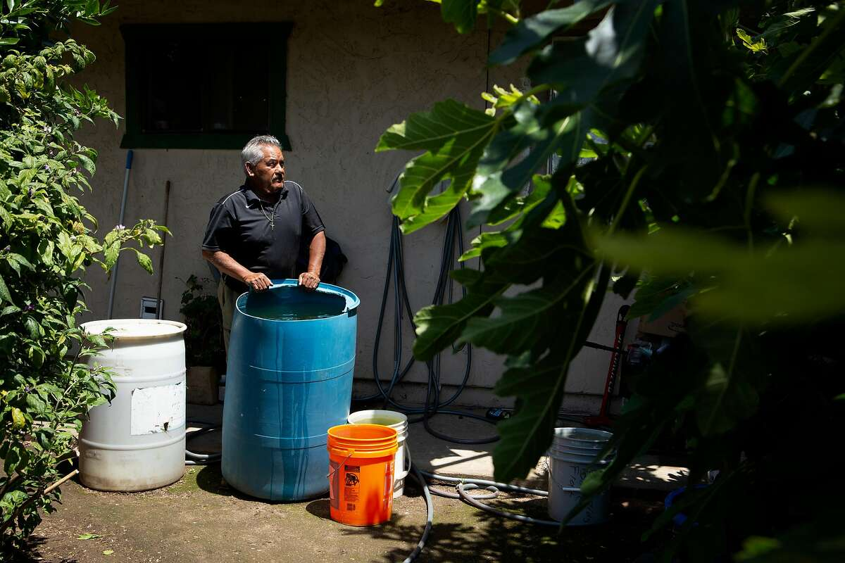 A portrait of Jose Hernandez at the San Jerardo Cooperative on Friday, May 24, 2019, in Salinas, Calif. Hernandez says his new water bill is expensive after the area implemented a new water system. Hernandez fears the water is still undrinkable and also relies on rain water and reusing the water from his wash-and-dry (blue bucket) to use on his garden and reduce his bill.