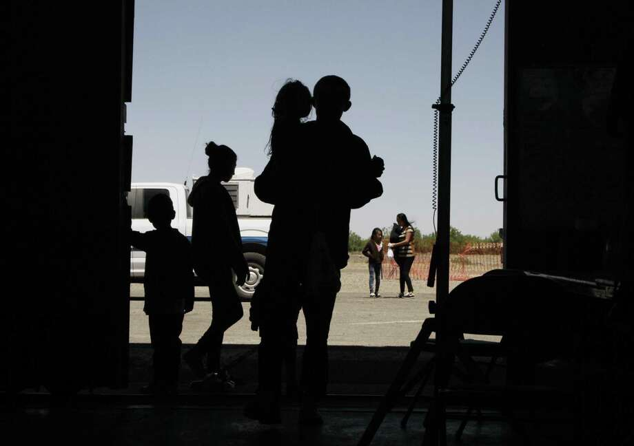 Migrants mainly from Central America guide their children through the entrance of a World War II-era bomber hanger in Deming, N.M., on May 22. The hysteria about immigration is often rooted in racist notions. Photo: Cedar Attanasio /Associated Press / Copyright 2019 The Associated Press. All rights reserved.
