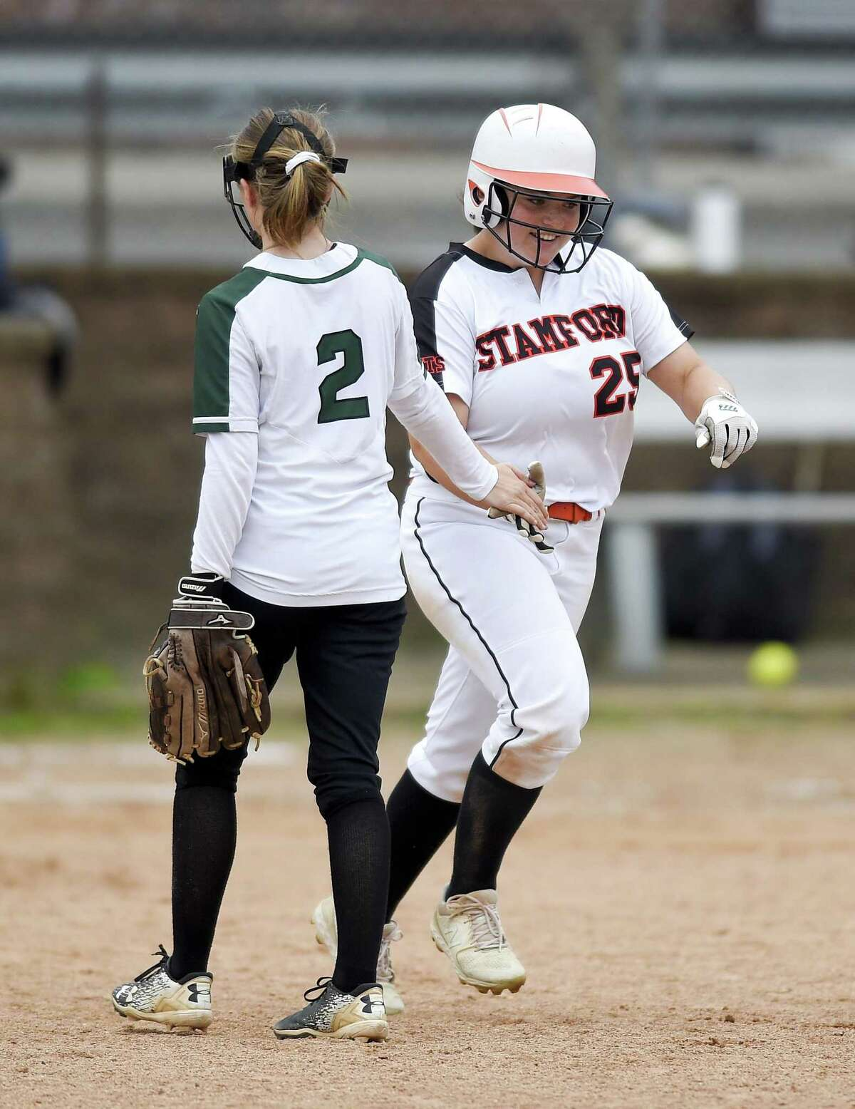 Stamford's Abby Hogan celebrates with New Milford's Sarah Mickelson as Hogan rounds the bases following a grand slam in the fifth inning in the Class LL state tournament at Stamford on Wednesday. Stamford won, 10-0.