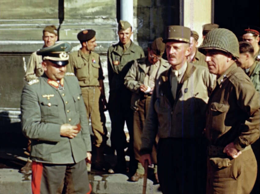 Gen. Phillippe Leclerc, foreground second right, stands with a captured German officer, left, after the liberation of Paris in 1944 during World War II. Seventy-five years later, surprising color images of the D-Day invasion and aftermath bring an immediacy to wartime memories. They were filmed by Hollywood director George Stevens and rediscovered years after his death. (War Footage From the George Stevens Collection at the Library of Congress via AP)