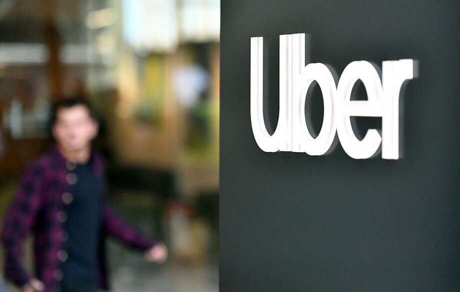 In this file photo taken on May 8, 2019, an Uber logo is seen on a sign outside the company's headquarters. Uber announced more than 400 layoffs in its engineering and product units Tuesday. Photo: Josh Edelson, AFP/Getty Images