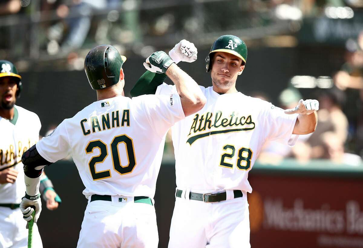 OAKLAND, CALIFORNIA - MAY 29: Matt Olson #28 of the Oakland Athletics is congratulated by Mark Canha #20 after he hit a two-run home run in the eighth inning against the Los Angeles Angels at Oakland-Alameda County Coliseum on May 29, 2019 in Oakland, California. (Photo by Ezra Shaw/Getty Images)