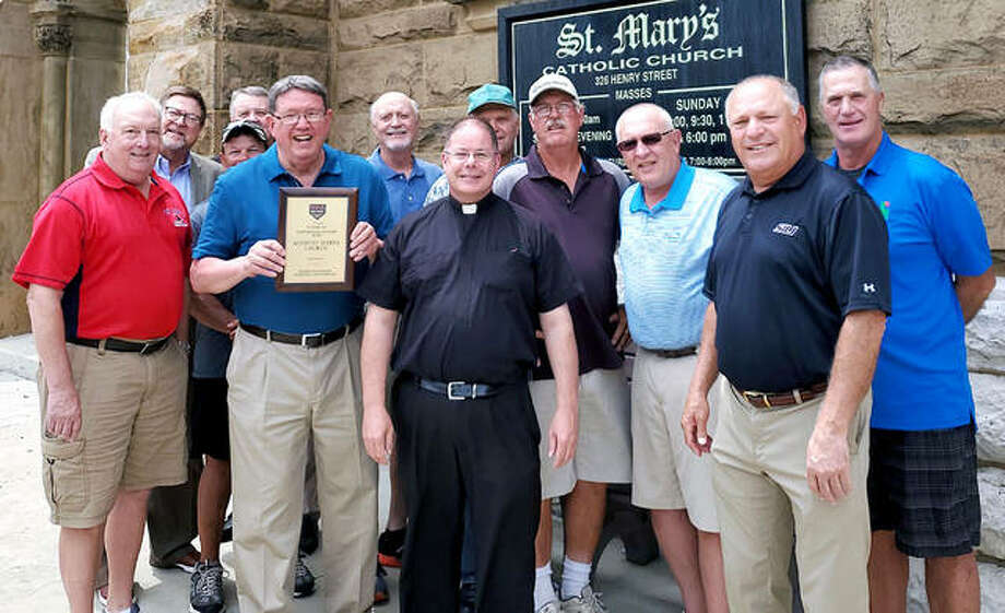 Members of the 1978 St. Mary's softball team gathers in front of the church earlier this week with its ASA Hall of Fame plaque. The team, which won the Amateur Softball Association of America Illinois state title that year for the first of four consecutive times, was recently inducted into the Illinois ASA Hall of Fame. From left are Dan Beiser, Mike Drake, Steve Angelo, Roger Lyons, Rick Faccin (with plaque), Neil Schultz, Father Jeremy Paulin OMV, Larry Ceppenati, Lonnie Wilson, Jim Mormino and Bob Perica. Photo: Submitted Photo