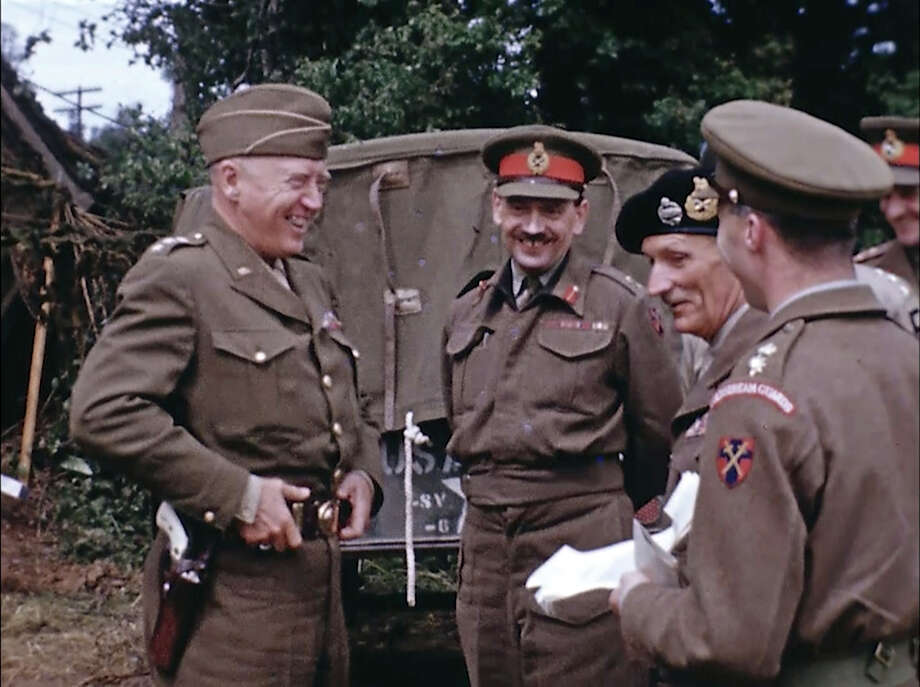 U.S. Army Gen. George Patton, left, with a pearl-handled pistol, talks to British Field Marshal Bernard Montgomery, center right with the beret hat, and other British officers in France during World War II. Seventy-five years later, surprising color images of the D-Day invasion and aftermath bring an immediacy to wartime memories. They were filmed by Hollywood director George Stevens and rediscovered years after his death. Photo: George Stevens/AP