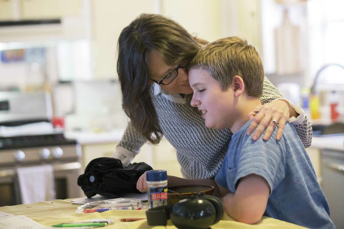 Bonnie Jensen kisses and says goodbye to her son Micah Jensen, 12, before leaving to meet with other mothers with special needs children who are excluded from the Texas' Compassionate Use Program in February 2018. Texas is close to passing a law that would legalize certain marijuana products, cannibinoid oil, with 0.3 percent or less of the pyschoactive ingredient THC; other bills that would expand the state's medical marijuana program, which allows doctors to prescribe up to 0.5 percent of those products, meanwhile, have stalled. ( Marie D. De Jesus / Houston Chronicle )