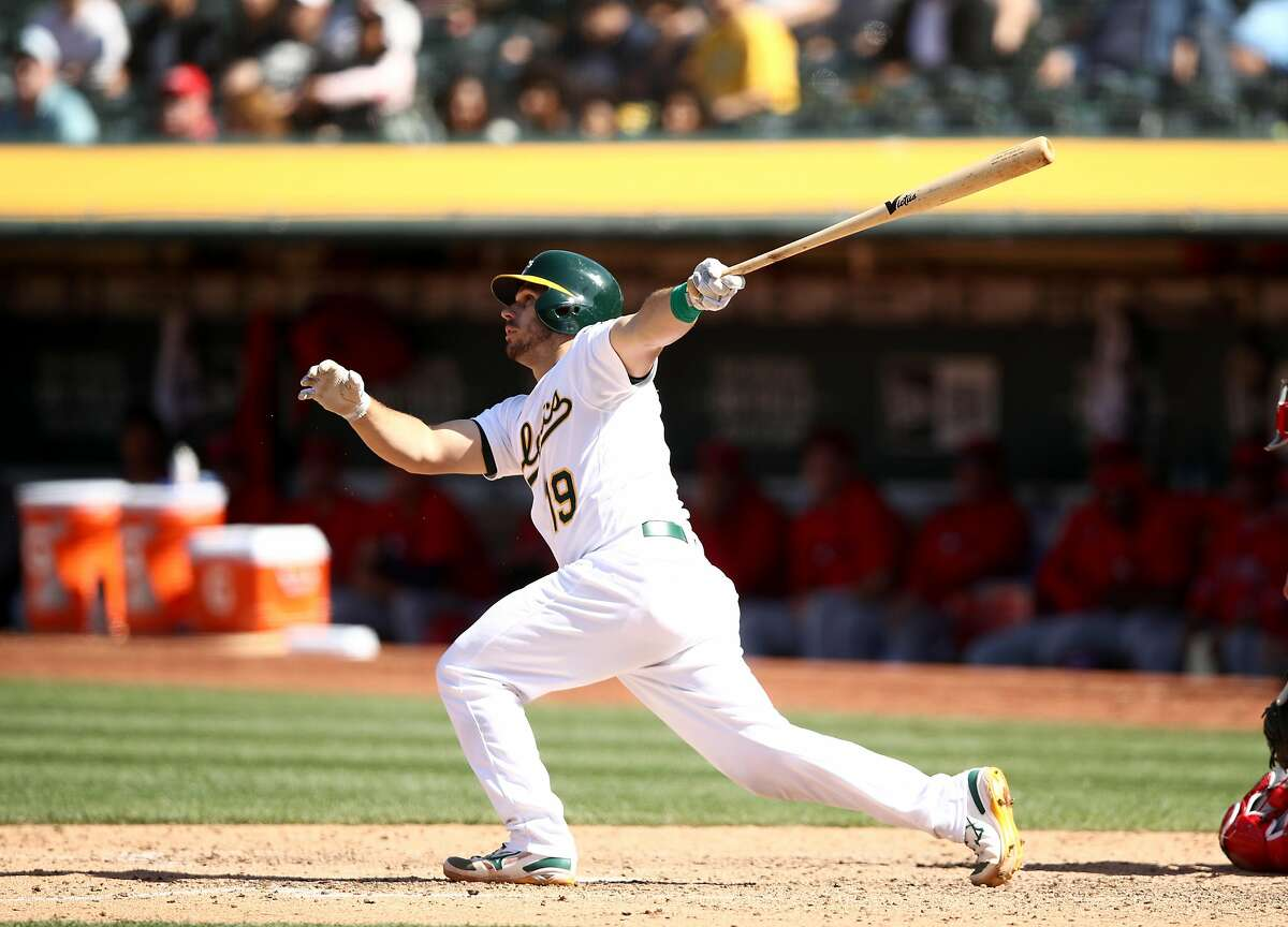 OAKLAND, CALIFORNIA - MAY 29: Josh Phegley #19 of the Oakland Athletics hits a sacrifice fly that scored a run to tie the game in the ninth inning against the Los Angeles Angels at Oakland-Alameda County Coliseum on May 29, 2019 in Oakland, California. (Photo by Ezra Shaw/Getty Images)