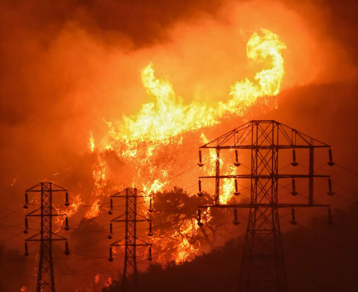 FILE - In this Dec. 16, 2017, file photo provided by the Santa Barbara County Fire Department, flames burn near power lines in Sycamore Canyon near West Mountain Drive in Montecito, Calif. State fire officials blame Pacific Gas & Electric Corp.'s equipment for starting more than a dozen California wildfires over the last two years. PG&E filed for bankruptcy in Jan. 2019, saying it faced at least $13 billion in legal claims from wildfire victims. (Mike Eliason/Santa Barbara County Fire Department via AP, File)