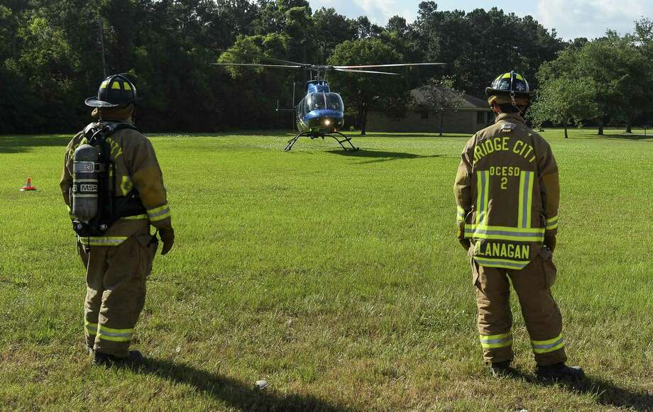 Two Bridge City firefighters watch a Southeast Texas Air Rescue helicopter land in a field near Highway 87 Wednesday evening. At 4:38 p.m. Bridge City Fire and Rescue got a call about a three vehicle five people involved in an accident at Highway 87 and Berwick Drive. Three of the occupants denied treatment, one was taken to a hospital via ambulance and a child was taken to a hospital via Southeast Texas Air Rescue. By 6:00 p.m. the site of the accident was clear and traffic, though backed up, was moving normally. Photo taken on Wednesday, 05/29/19. Ryan Welch/The Enterprise Photo: Ryan Welch, Beuamont Enterprise / The Enterprise / © 2019 Beaumont Enterprise