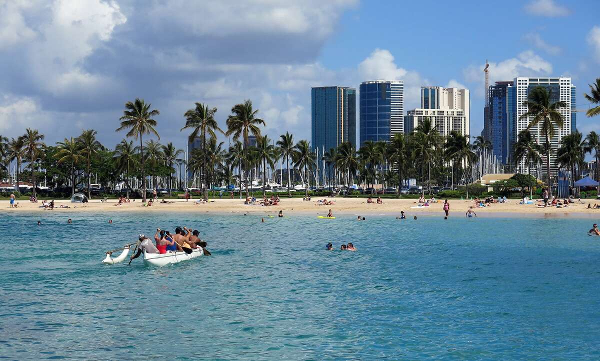 FILE - This May 21, 2014, file photo shows Duke Kahanamoku Beach in the Honolulu tourist neighborhood of Waikiki in Hawaii. A Hawaii-based travel agency is under investigation after Bay Area residents reported losing thousands of dollars in travel arrangements they never received.