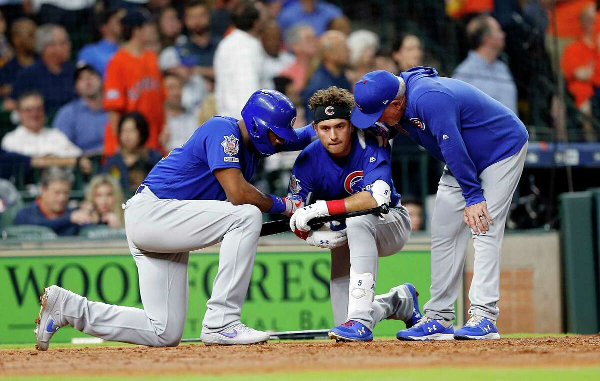HOUSTON, TEXAS - MAY 29: Albert Almora Jr. #5 of the Chicago Cubs is comforted by manager Joe Maddon #70 and Jason Heyward #22 after a young child was injured on foul ball off his bat in the fourth inning against the Houston Astros at Minute Maid Park on May 29, 2019 in Houston, Texas.