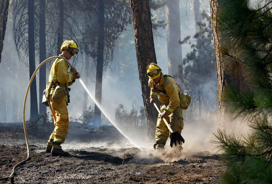 Firefighters douse hot spots along highway 120 near Groveland, Calif. on Wednesday August 28, 2013, during the Rim Fire in the Stanislaus National Forest. Photo: Michael Macor / The Chronicle 2013