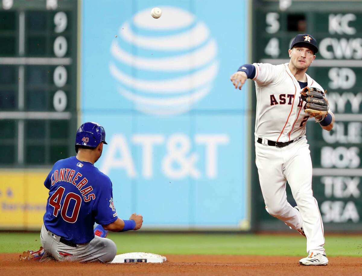 Houston Astros shortstop Alex Bregman (2) turns a double play over Chicago Cubs catcher Willson Contreras (40) during the fourth inning of a major league baseball game at Minute Maid Park on Wednesday, May 29, 2019, in Houston.