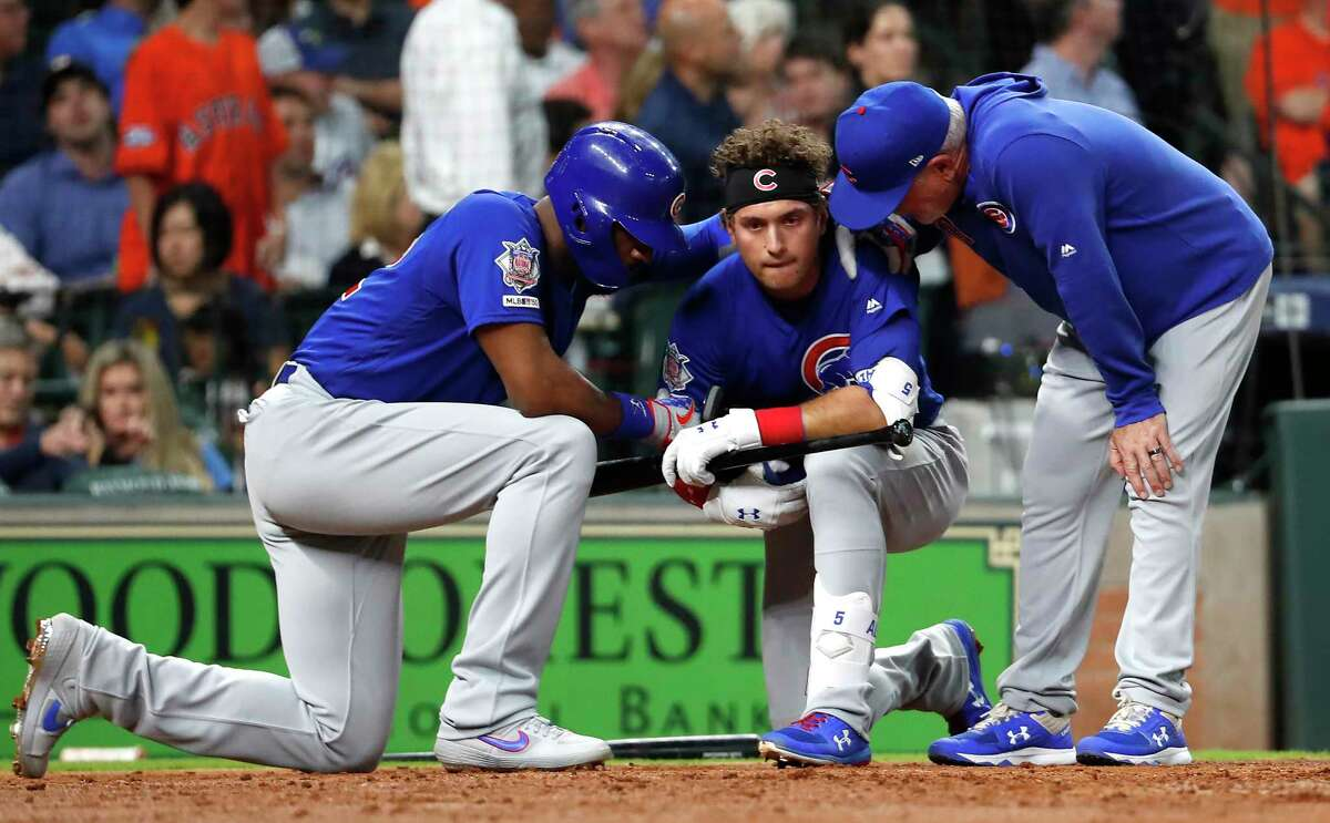 Chicago Cubs center fielder Albert Almora Jr., center, comforted by Cubs right fielder Jason Heyward and manager Joe Maddon, as he drops to a knee after a foul ball he hit into the stands hit a small child during the fourth inning of a major league baseball game against the Houston Astros at Minute Maid Park on Wednesday, May 29, 2019, in Houston.