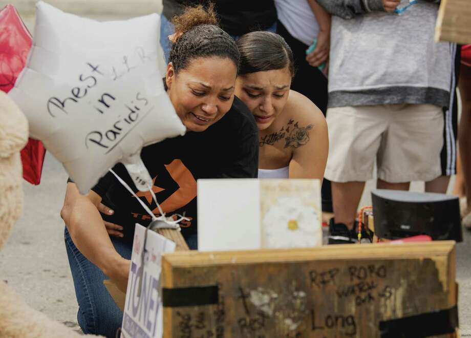 "The mother of Sebastian ""Roro"" Montez, left, and another family member, right, react during a vigil held by friends and family at the corner of Hays and Lockhart streets on Wednesday, May 29, 2019. Her son was killed the day prior in a drive-by shooting. Photo: Carlos Javier Sanchez / Contributor / Carlos Javier Sanchez"