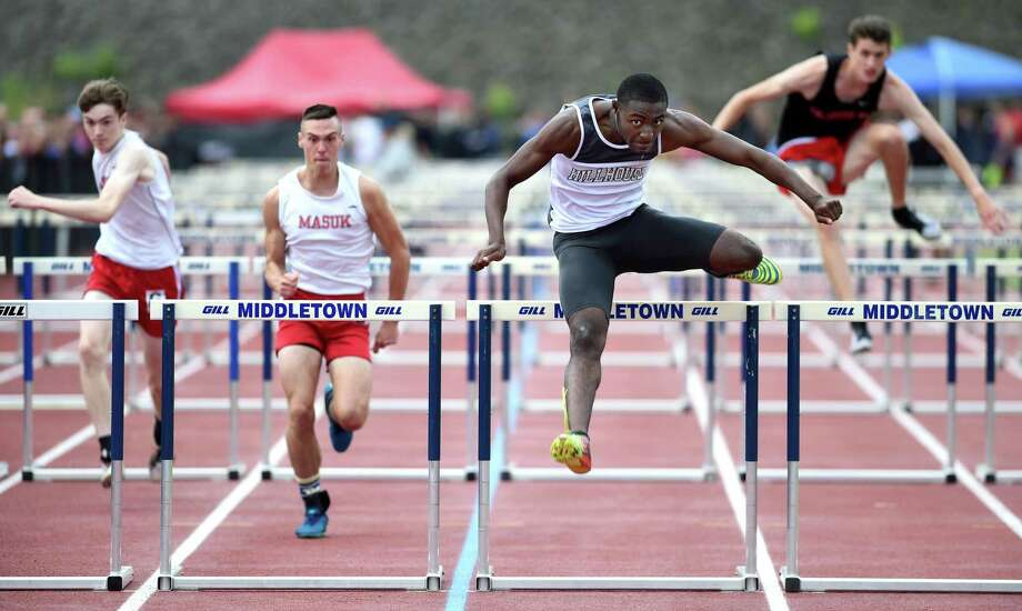 Hillhouse's Deshaune Poole, center, runs to a first place finish in the 110 meter hurdles in the Class MM campionship. Photo: Arnold Gold / Hearst Connecticut Media / New Haven Register