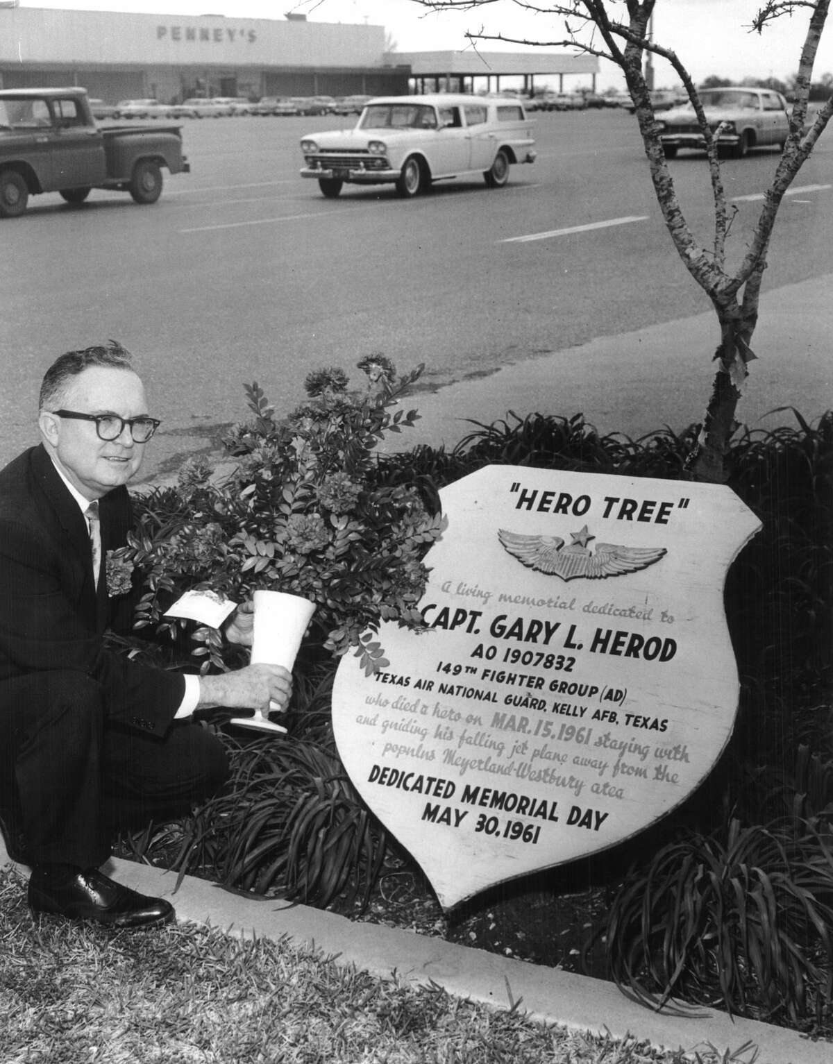 Circa March 1963: William R. Byers, of 5234 Cheena, president of the Myerland Merchants Exchange, is shown placing a vase of flowers at the base of the