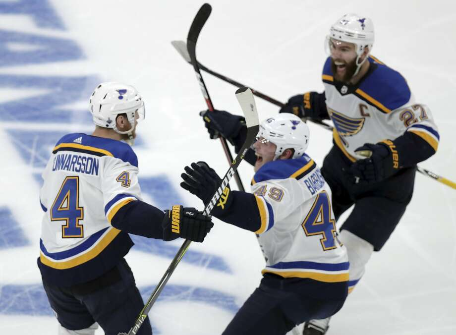 The Blues' Carl Gunnarsson (4), of Sweden, is congratulated by Ivan Barbashev (49), of Russia and Alex Pietrangelo, right, after he scored the winning goal against the Boston Bruins during the first overtime period in Game 2 of the NHL hockey Stanley Cup Final, Wednesday, May 29, 2019, in Boston. (Bruce Bennett/Pool via AP) Photo: Bruce Bennett / Associated Press