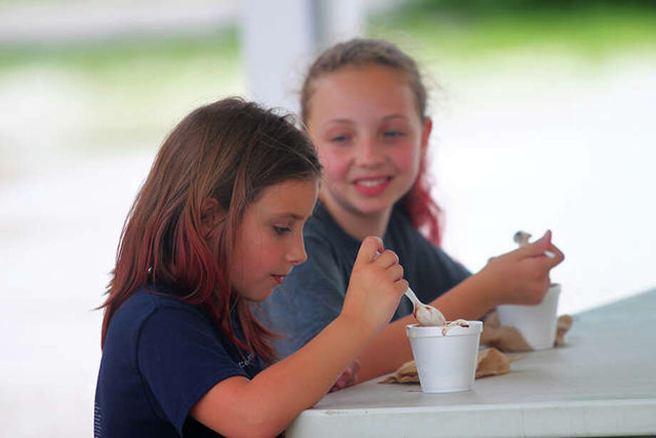 Sisters Livia and Joselynn Cooper of White Hall eat ice cream with their grandparents Wednesday at The Ice Cream Depot in Roodhouse. Photo: Rosalind Essig | Journal-Courier