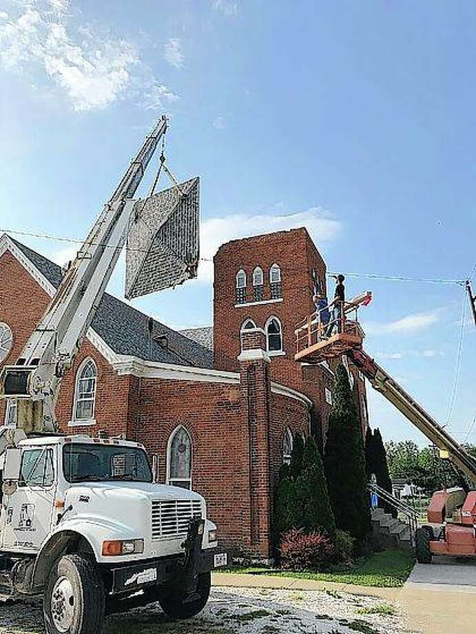 Crews work to clean up the damage at First Baptist Church in Roodhouse this week. The bell tower roof was lifted by strong winds and thrown onto the roof of the church Saturday evening. Photo: Photo Provided
