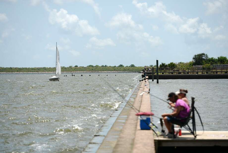 Anglers fish Sabine Lake as a sailboat heads back into the docks Saturday afternoon. Warm weather brought anglers out to the water's edge on Pleasure Island on Saturday. The Saltwater Anglers League of Texas also held a Fishing Rodeo event over the weekend. Photo taken Saturday 5/24/14 Jake Daniels/@JakeD_in_SETX Photo: Jake Daniels / ©2014 The Beaumont Enterprise/Jake Daniels