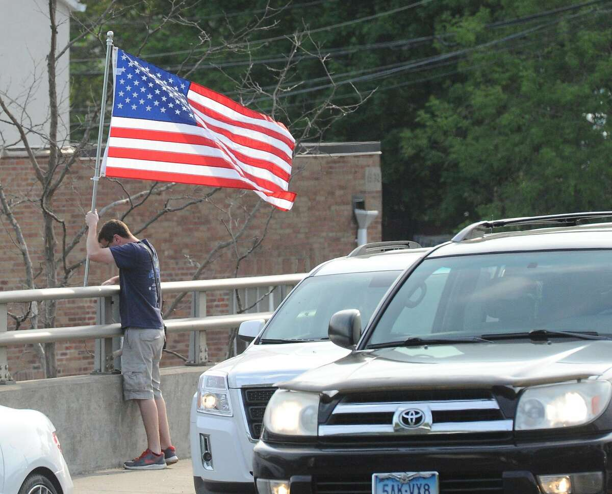 Cos Cob Volunteer Firefighter Lt. Kevin Ingraham places an American Flag during the annual tradition of putting up American flags on the Dave Theis memorial bridge that connects the Greenwich communities of Cos Cob and Riverside, Conn., Thursday, May 26, 2016. President of the Cos Cob Volunteer Firefighters, Steve Francefort, one of the organizers of the event, said the 20 flags that were placed on the bridge were donated by Greenwich residents, husband and wife, Joe and Barbara Havranek.