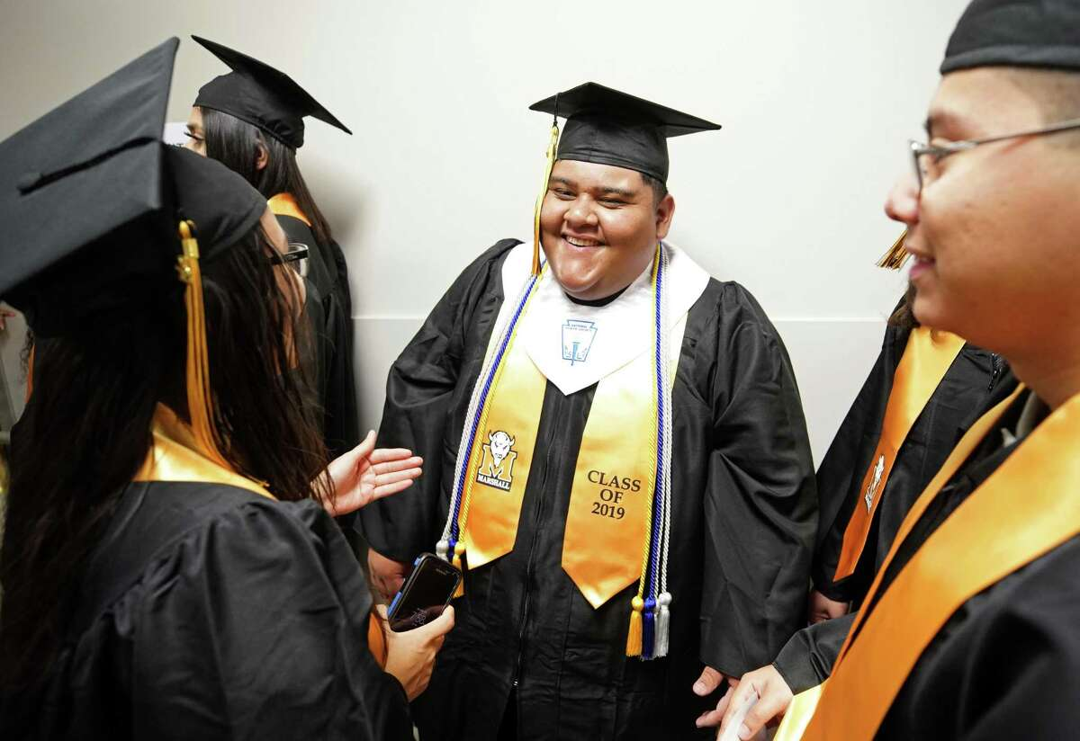 Thurgood Marshall High School students Anna Majano, 18, left, Jose Lopez, 19, and Carlos Lopez, 18, right, wait in line for graduation ceremony at Smart Financial Centre, 18111 Lexington Blvd., Saturday, May 25, 2019, in Sugar Land.